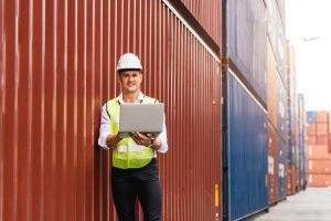 foreman holding document walking checking containers box from cargo ship export import