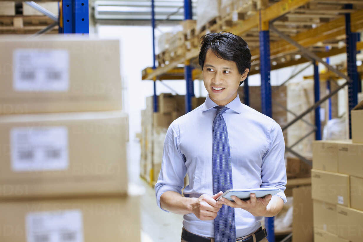 mid adult male manager using digital tablet in distribution warehouse CUF35023