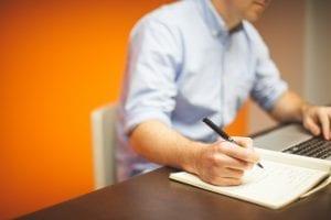 gambar tangan sedang menulis untuk menjelaskan apa itu arti distributor