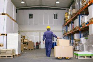 senior logistic worker hardhat uniform walking warehouse wheeling palette jack back view full length labor logistics concept 1