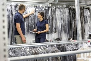 two warehouse workers using digital tablet to stock take garments in distribution warehouse CUF31416