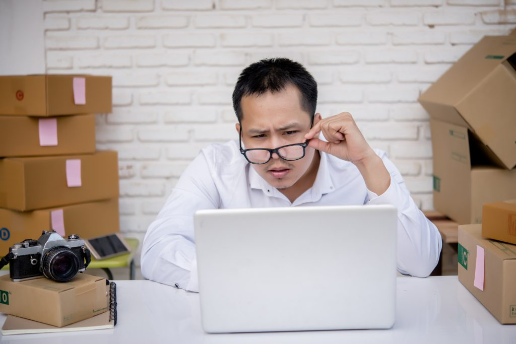 young man working marketing online with laptop box post